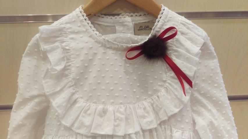 Detalle blusa plumeti con pompon y lazada